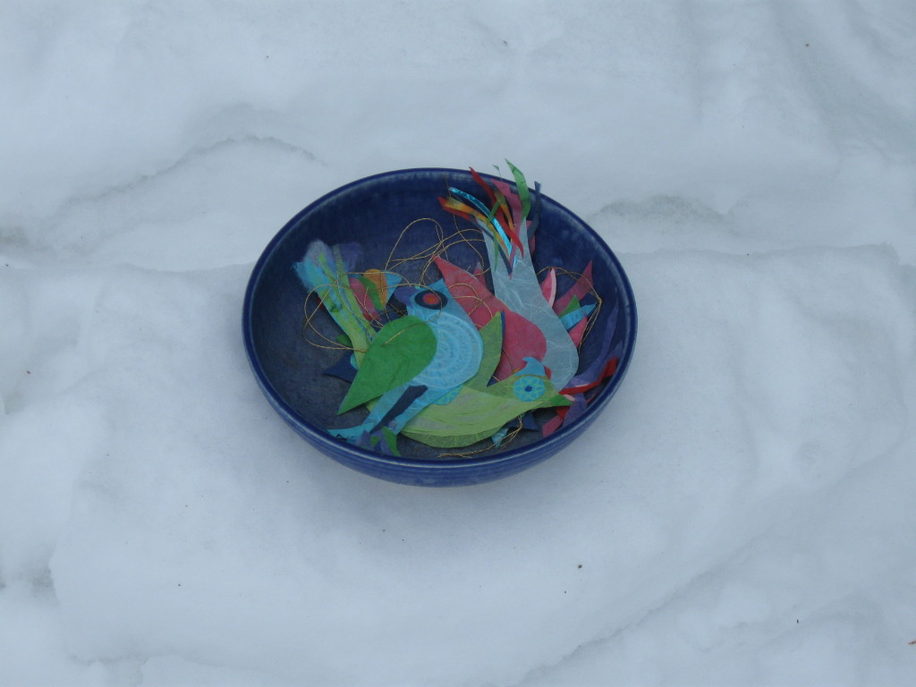 birds in blue bowl in snow