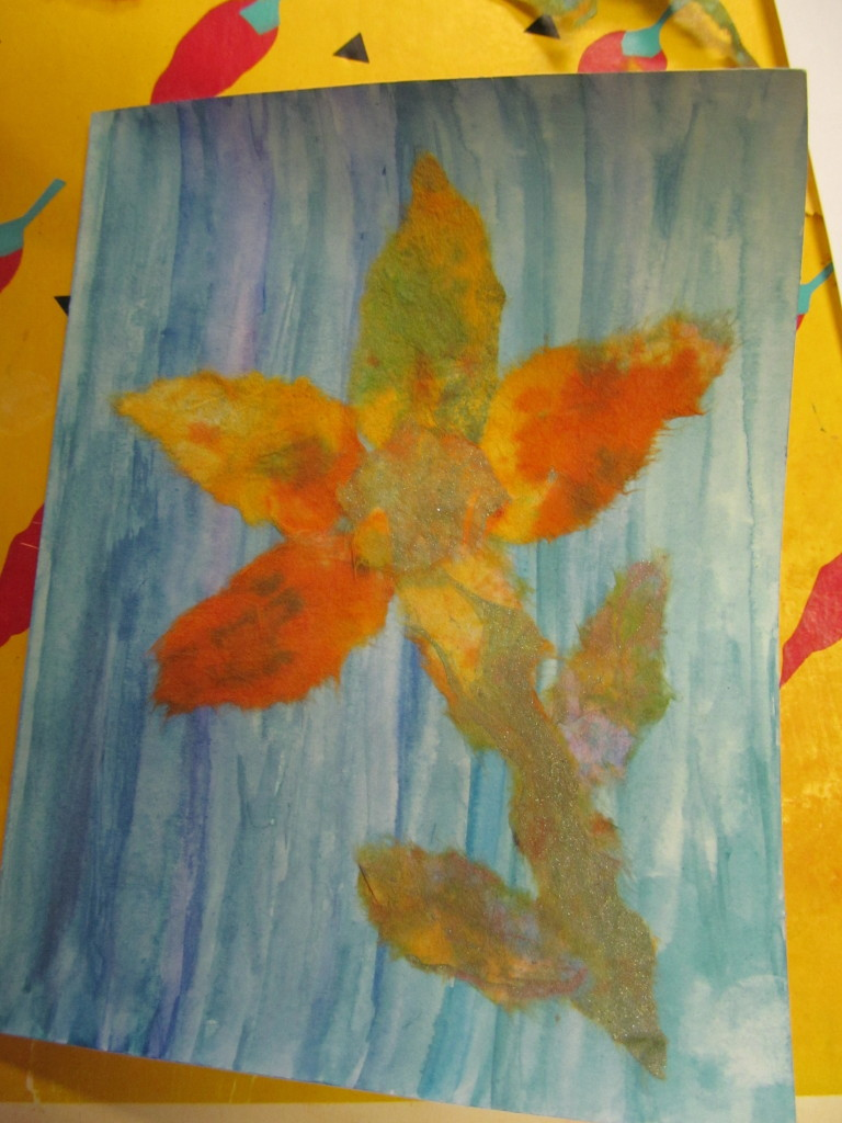 Joan experiments with watercolours on rice paper for the background, and voila, a flower blooms!